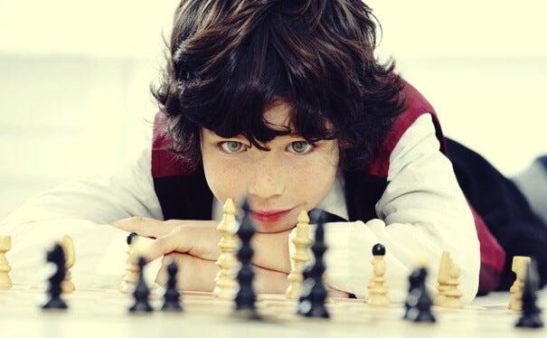 Niño mirando piezas de ajedrez simbolizando el el cerebro de los niños superdotados