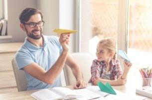 Padre e hija lanzando aviones de papel