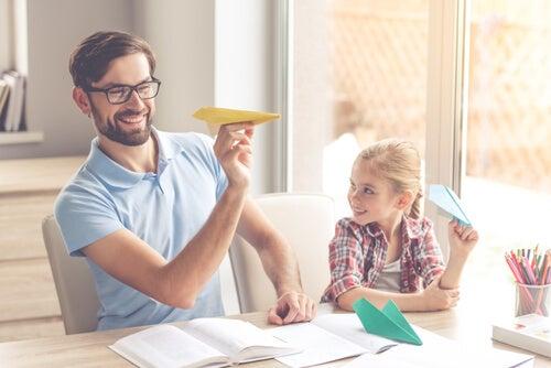 Padre e hija lanzando aviones de papel como método de distracción