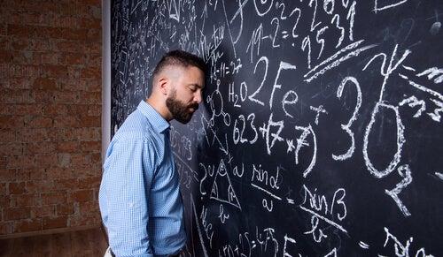 Profesor apoyando su cabeza en la pizarra