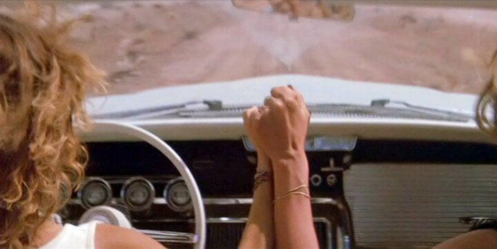 Thelma y Louise agarradas de la mano en el coche