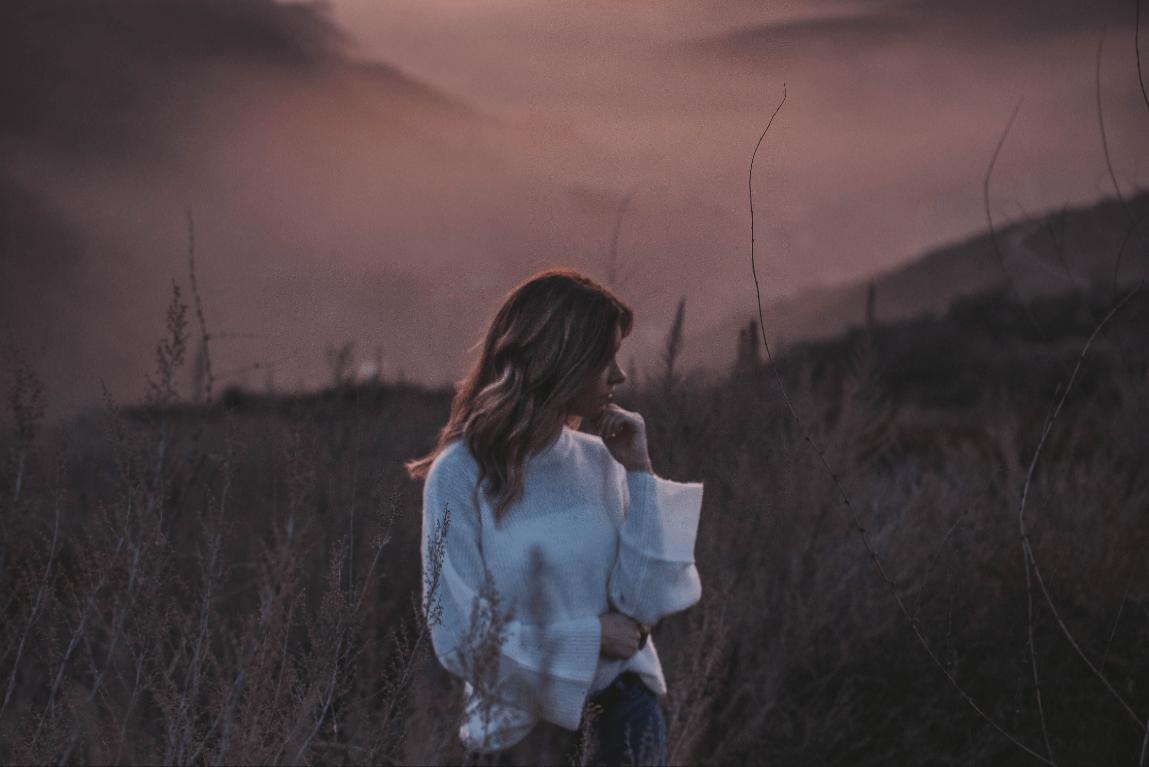 mujer pensando al atardecer y en la disonancia cognitiva