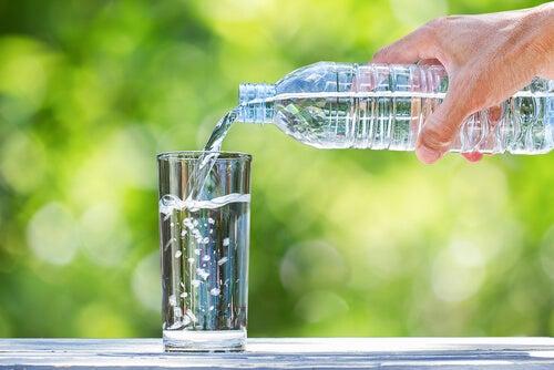 Botella echando agua en un vaso