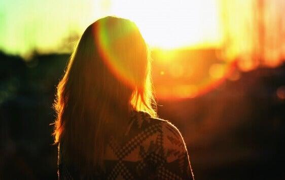 Chica de espaldas al amanecer