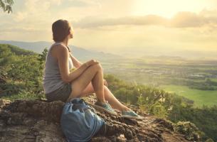 Chica en la montaña tomándose cinco minutos de silencio