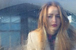 Chica triste ventana pensando en que su ex se fue sin decir adiós