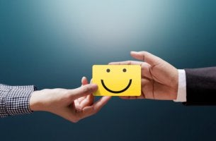 Empresario y cliente sujetando nota con una cara sonriente