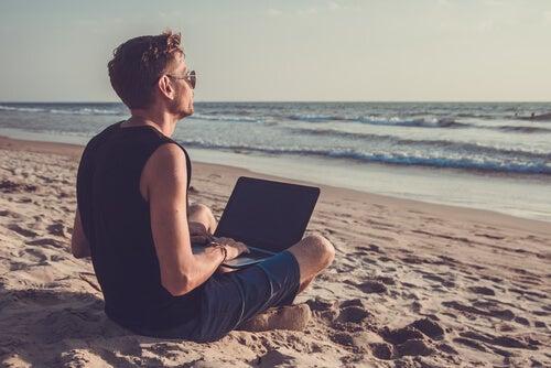Hombre en la playa con un portatil