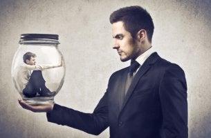 Hombre sujetando un frasco con otro hombre en su interior