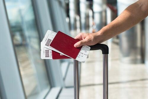 Mano de una persona con billetes para viajar