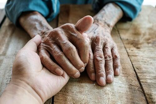 Manos de una persona adulta y una persona mayor durante la terapia de reminiscencia