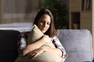 Mujer abrazada a un cojín comiéndose la cabeza