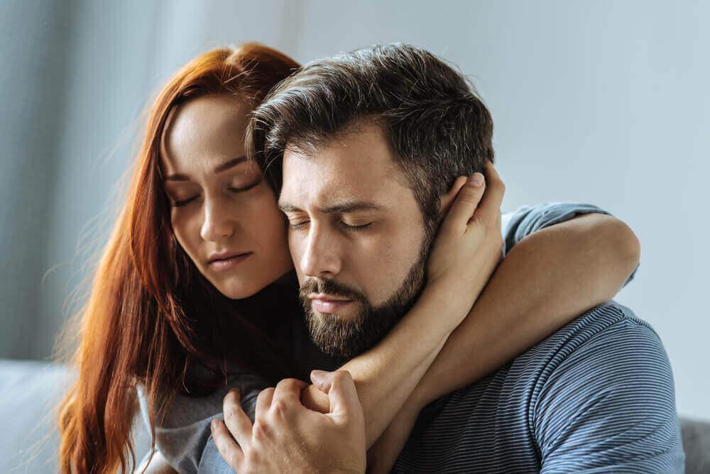 Mujer abrazando a un hombre con los ojos cerrados