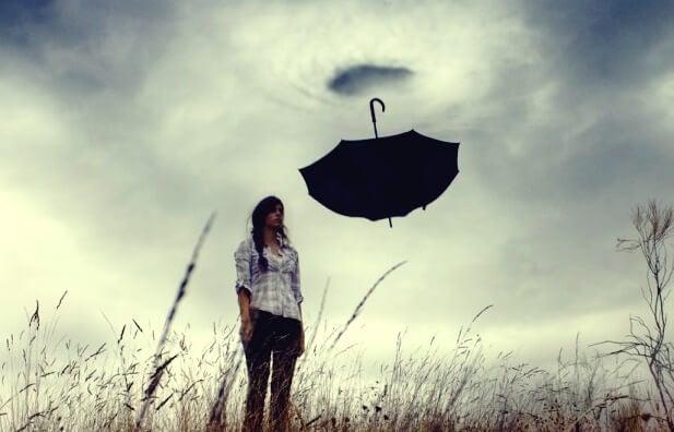 mujer ante paraguas que sufre angustia emocional