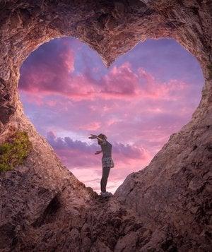 Mujer con los brazos abiertos en una cueva con forma de corazón