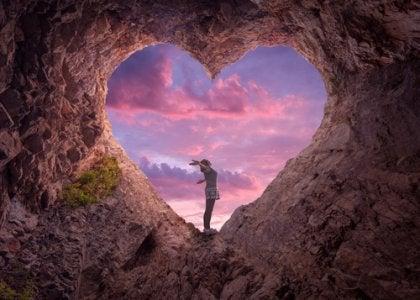 Mujer con los brazos abiertos en una cueva con forma de corazón simbolizando que la felicidad está en tu hemisferio izquierdo
