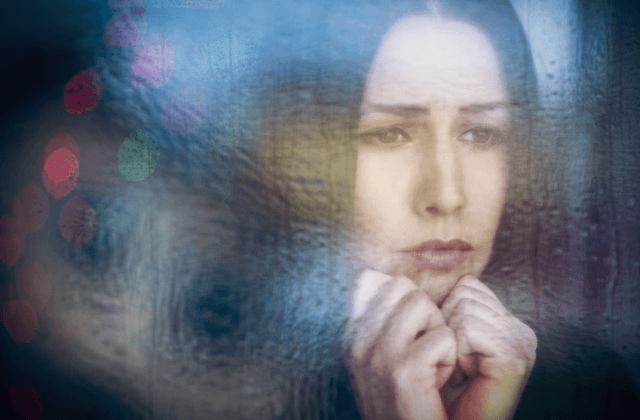 Mujer triste mirando por la ventana