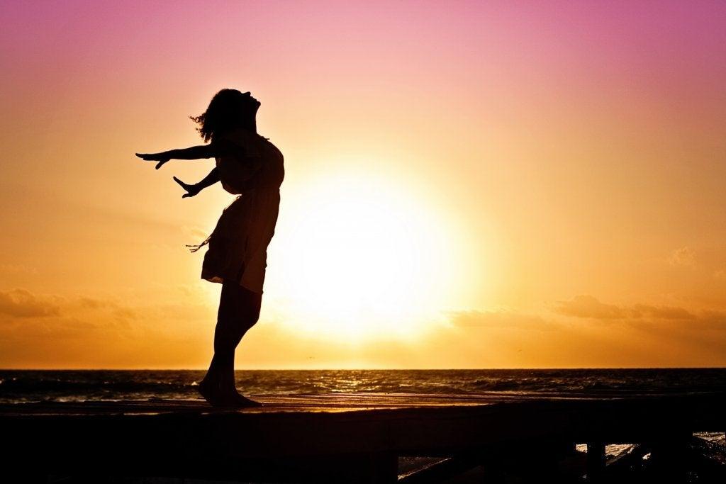 mujer al amanecer simbolizando cómo ser más felices después de la mediana edad