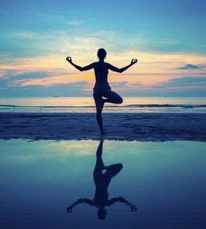 Mujer en equilibrio en la playa para representar el equilibrio psicológico