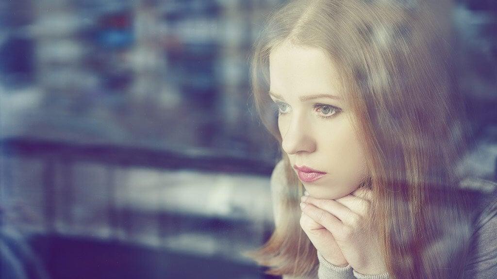 Mujer mirando por la ventana pensando que no puedo llorar