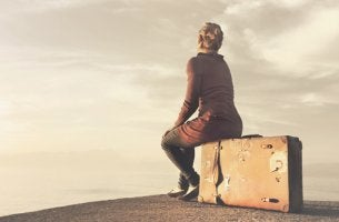 Mujer sentada sobre una maleta