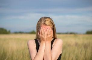 Mujer triste con las manos en la cara mientras piensa cómo combatir la necesidad de aprobación