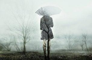 Mujer triste de espaldas bajo un paraguas