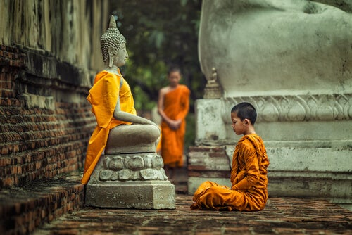 Niño frente a una figura de Buda