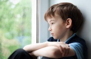 Niño triste mirando por la ventana