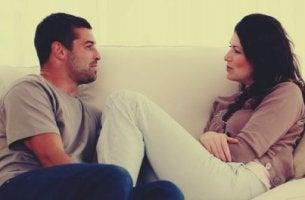 Pareja hablando sentados en el sofá
