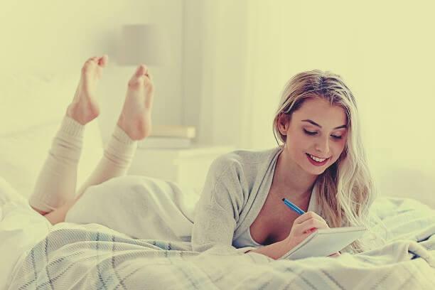 Chica en la cama escribiendo el diario de los 5 minutos