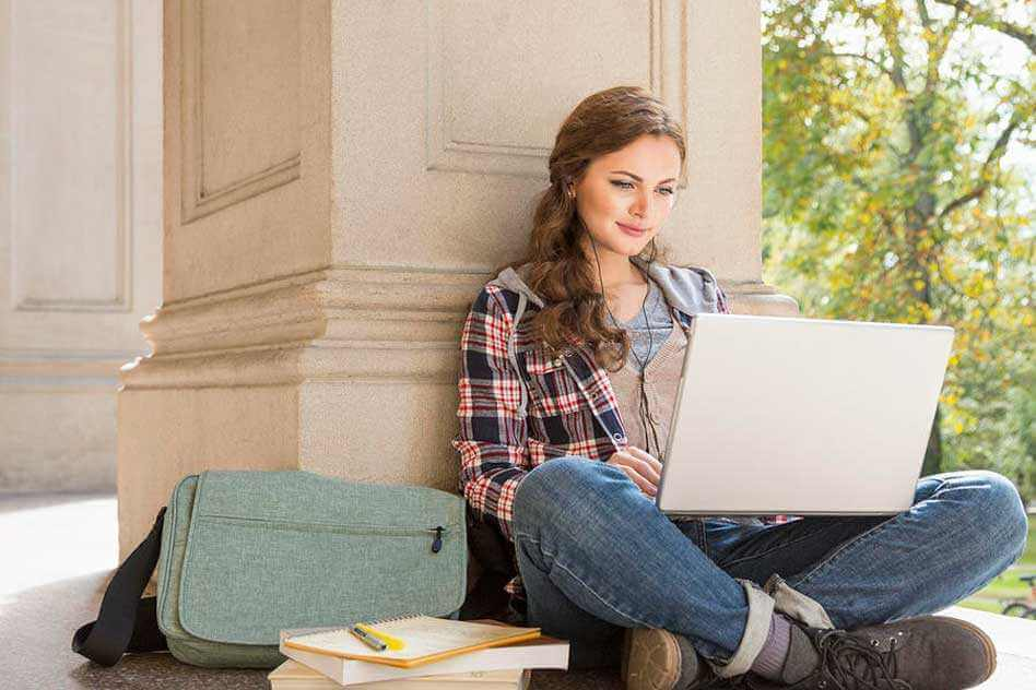 chica apoyada en un pilar y con ordenador que intenta combatir el aburrimiento al estudiar