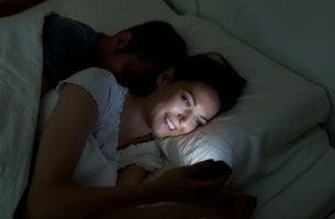 Chica mirando el móvil por la noche para representar la causa del insomnio digital