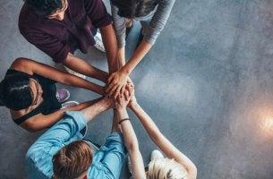 Compañeros de trabajo uniendo manos para representar la holocracia