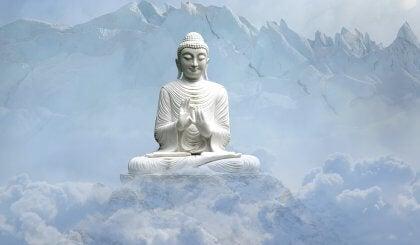 Escultura de Buda sobre una montaña rodeado de nubes