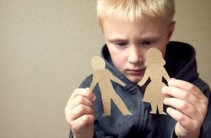 Hijo mirando figuras de padres para representar el concepto de desintegración familiar