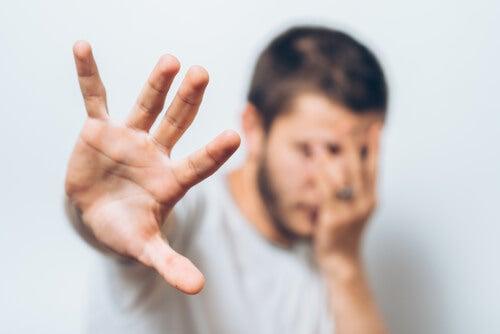 Hombre con miedo a la violencia intragénero cubriéndose