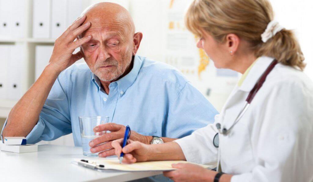 Hombre mayor con demencia hablando con su médico