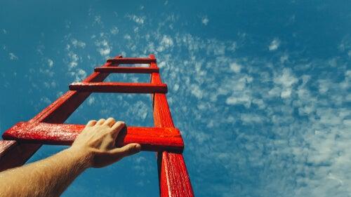 Hombre subiendo por una escalera hacia el cielo para representar la teoría del Grit