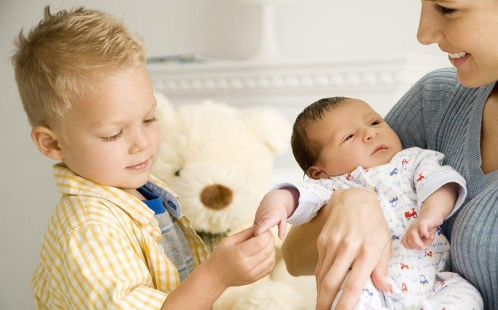 niño tocando a un bebé representando los celos cuando llega un nuevo hermano