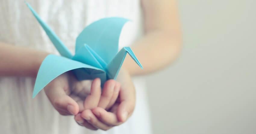 mano con pajarita de papel simbolizando la idea de ¿pides perdón con frecuencia?