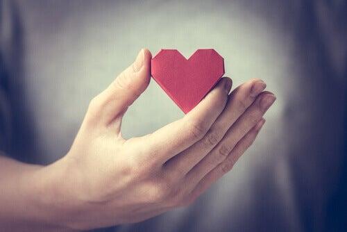 Mano sujetando un corazón rojo