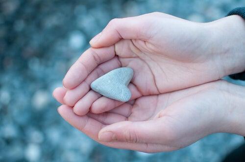 Manos con un corazón de piedra para representar las relaciones afectivas