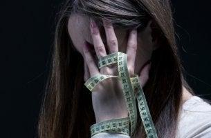 Mujer con anorexia con un metro en la cara para representar la sadorexia