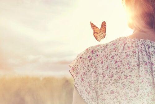 Mujer con una mariposa en el hombro pensando que todo cambia