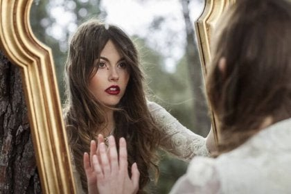 Mujer con miedo a la soledad mirándose a un espejo