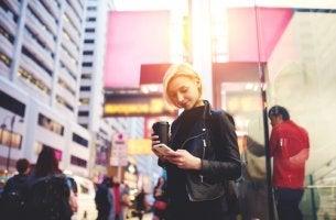 Mujer mirando el móvil mientras pasea representando el concepto de zombiewalking