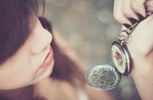 Mujer mirando un reloj por el síndrome de la felicidad aplazada