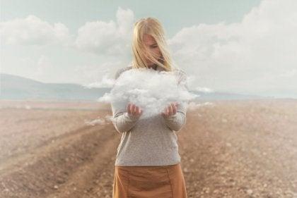 Mujer con una nube entre sus manos pensando en los problemas emocionales que tiene