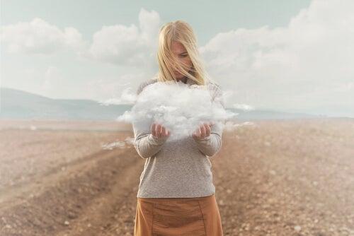 Mujer con una nube entre sus manos simbolizando el pensamiento catastrófico